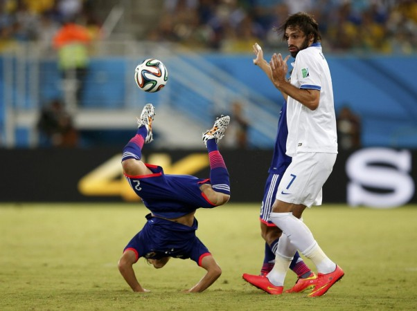 japans-atsuto-uchida-does-a-handstand-during-a-game-against-greece